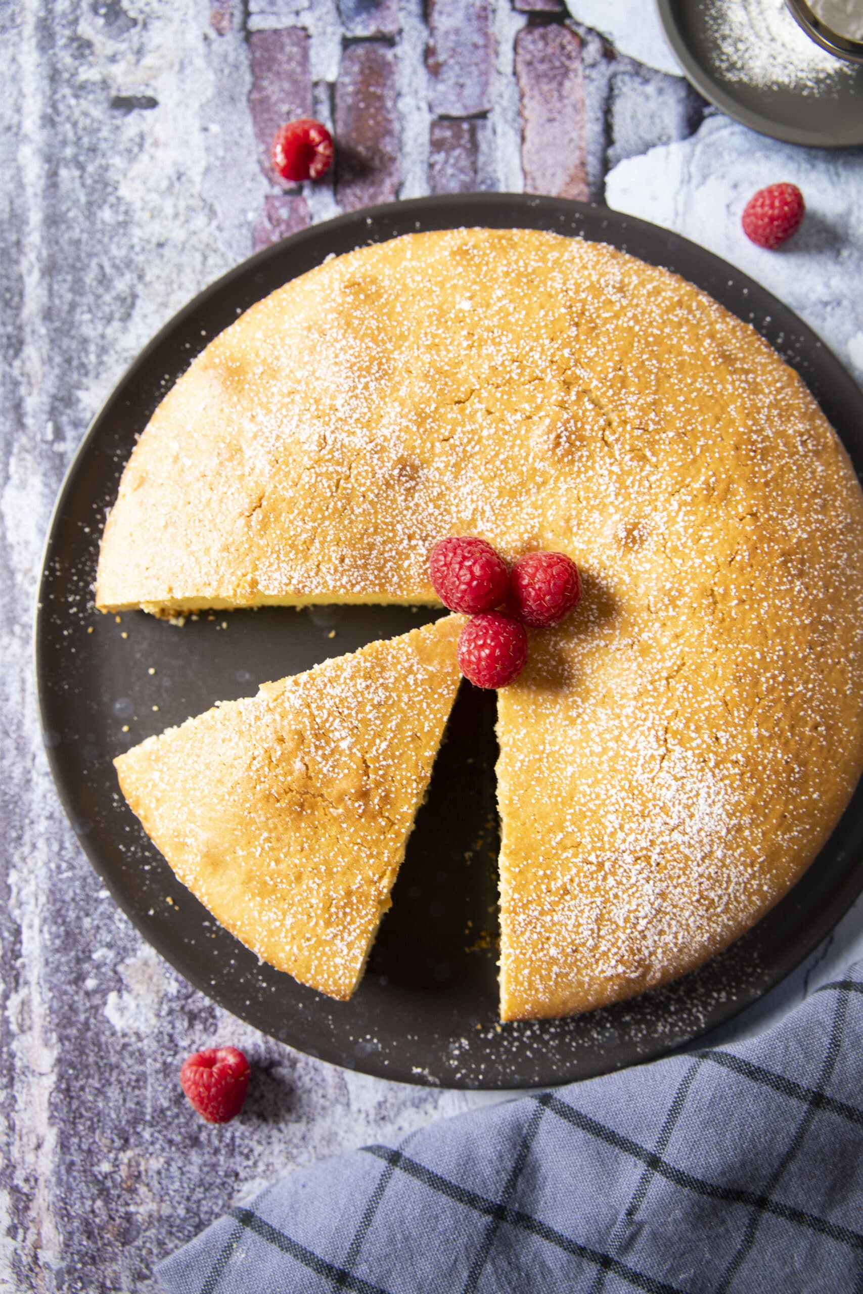 An overhead shot of a newly baked olive oil cake, with some slices already served.