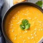 An overhead shot of a bowl of creamy sweet potato coconut soup, served with some chunky bread.