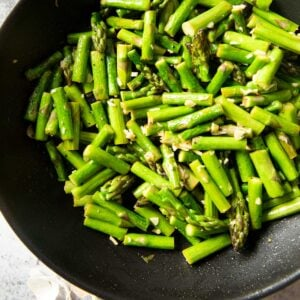 A closer shot of a pan of Sauteed Asparagus, highlighting the bits of garlic in the dish.