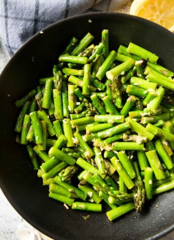 An overhead shot of a pan of newly cooked Sauteed Asparagus with Garlic, with a squeezed half lemon on the side.