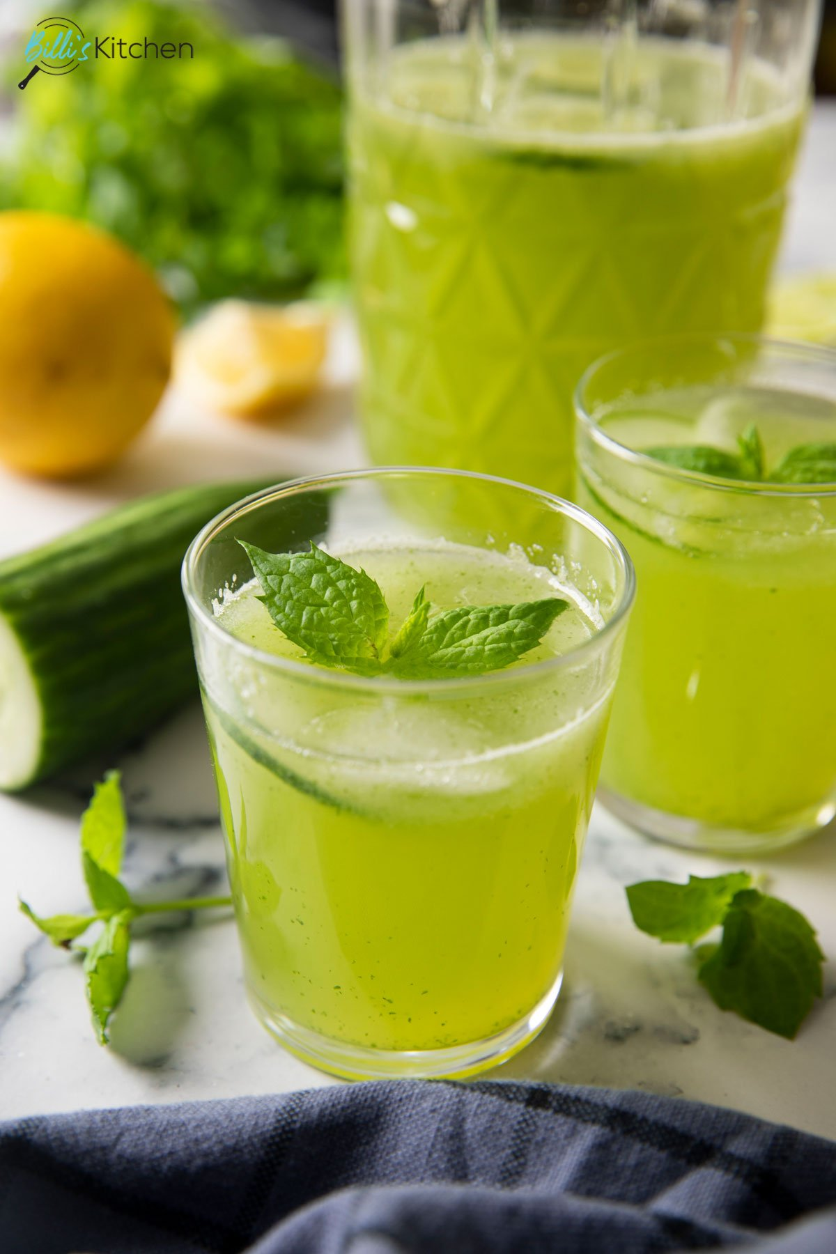 An image showing two glasses of Cucumber Mint Lemonade, and a pitcher half filled with it.