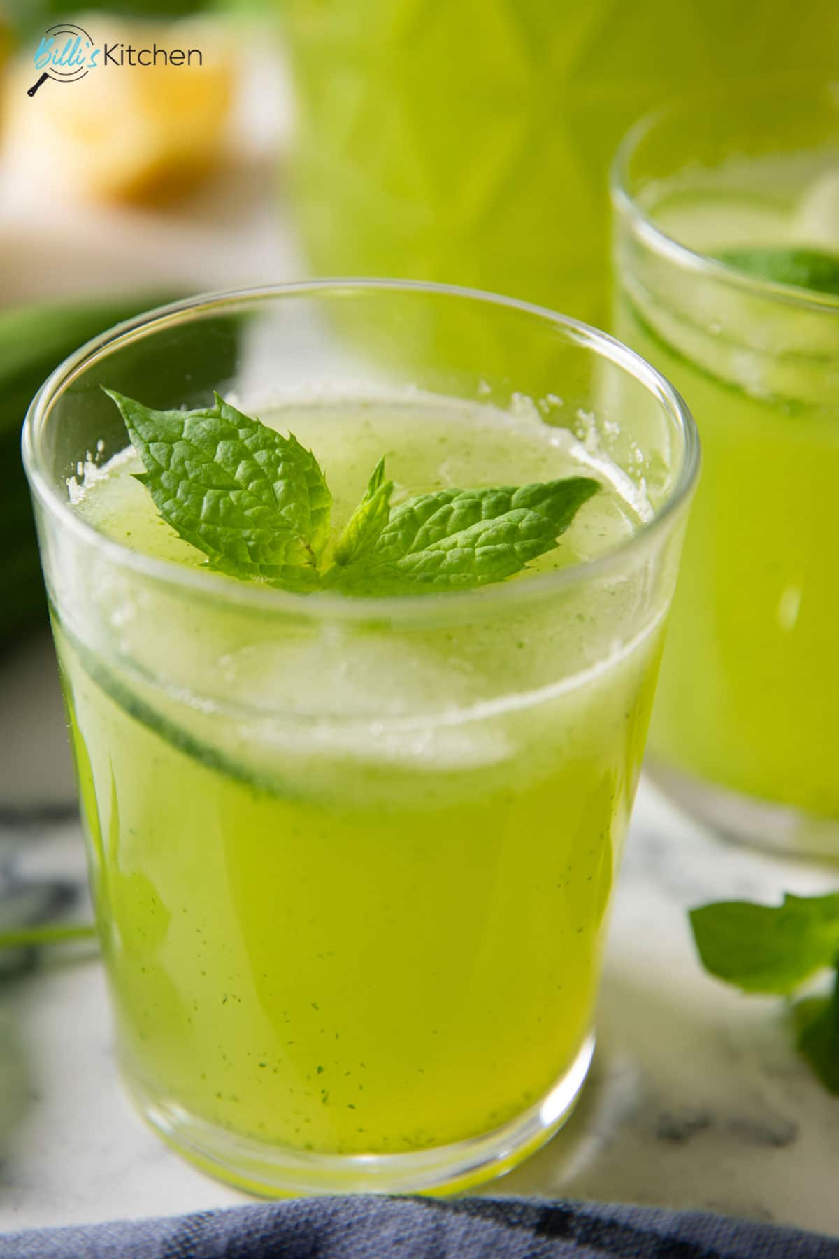 A closer shot of a glass of Cucumber Lemonade, highlighting the brightness of it, garnished with mint leaves.