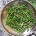 An overhead shot of a pan of just cooked Green Beans with Garlic, ready for serving.