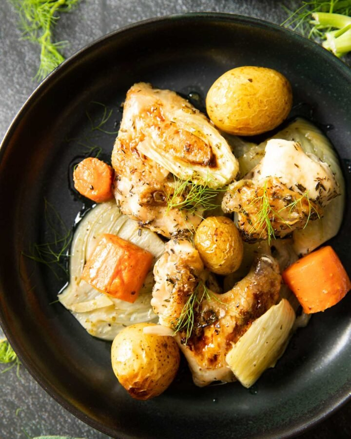 An overhead shot of a plate of Herb Roasted Chicken and Fennel, with some more fennel fronds on the table.