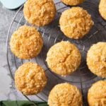 An overhead shot of freshly baked lemon muffins, cooling on a rack.