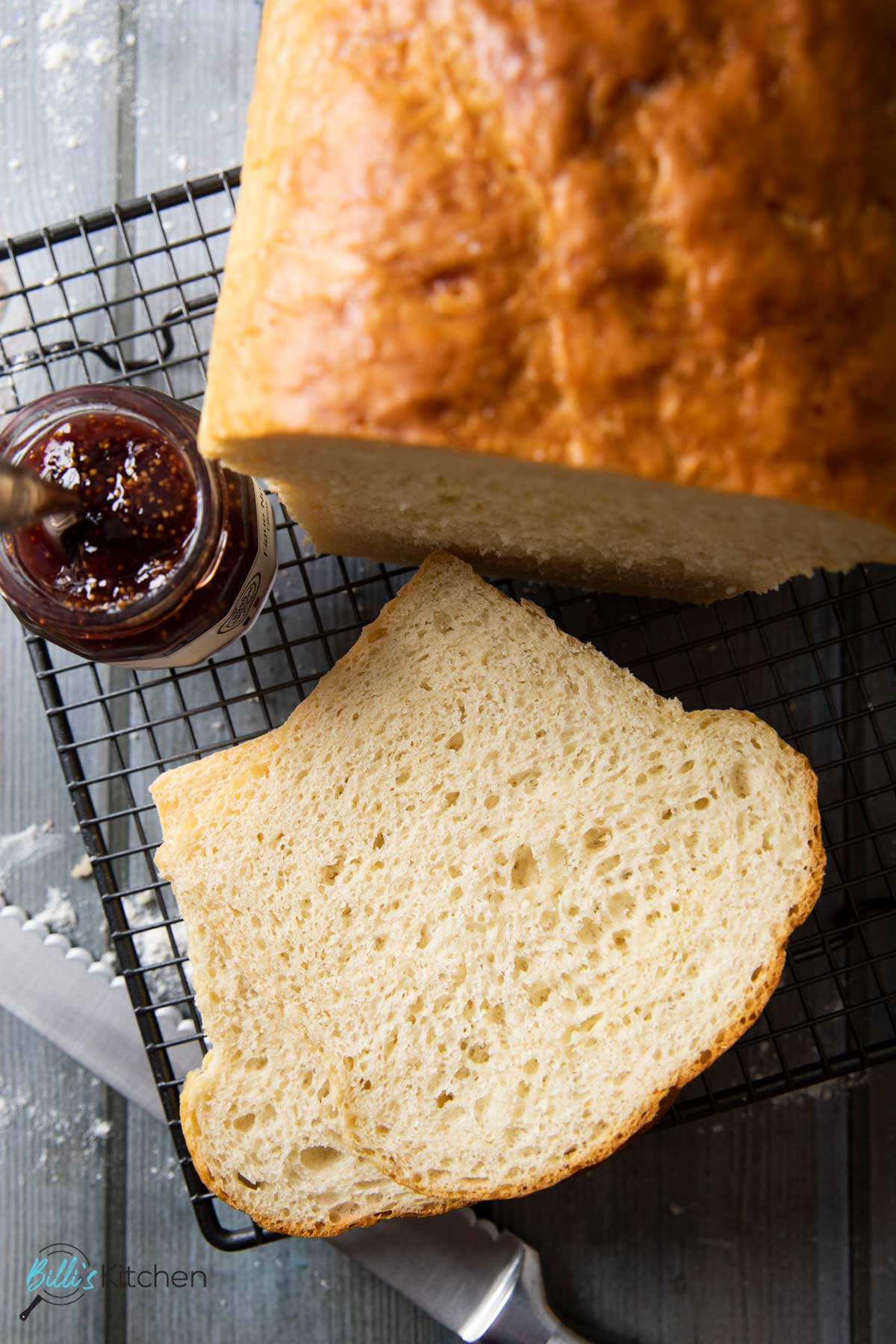An overhead shot of a couple of slices of homemade white bread, with a bottle of jam on the side, ready for spreading on the bread.