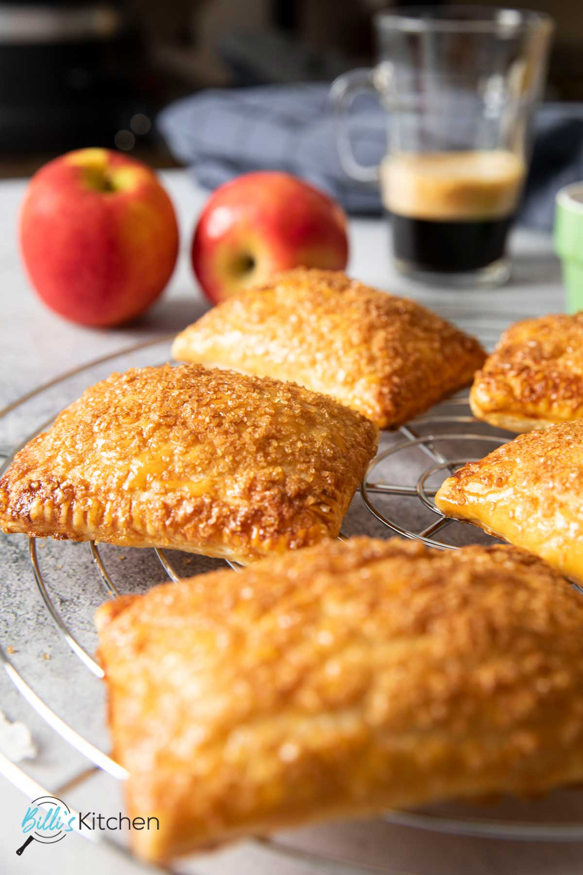 Freshly baked apple turnovers with puff pastry, cooling on a rack, ready for serving.