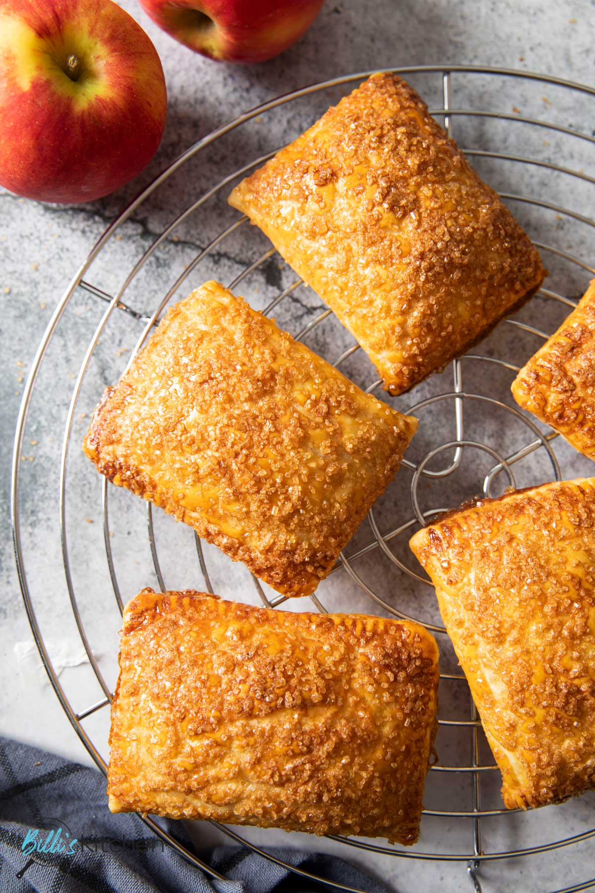 An overhead shot of golden brown apple turnovers, generously sprinkled with brown sugar; on a cooling rack.