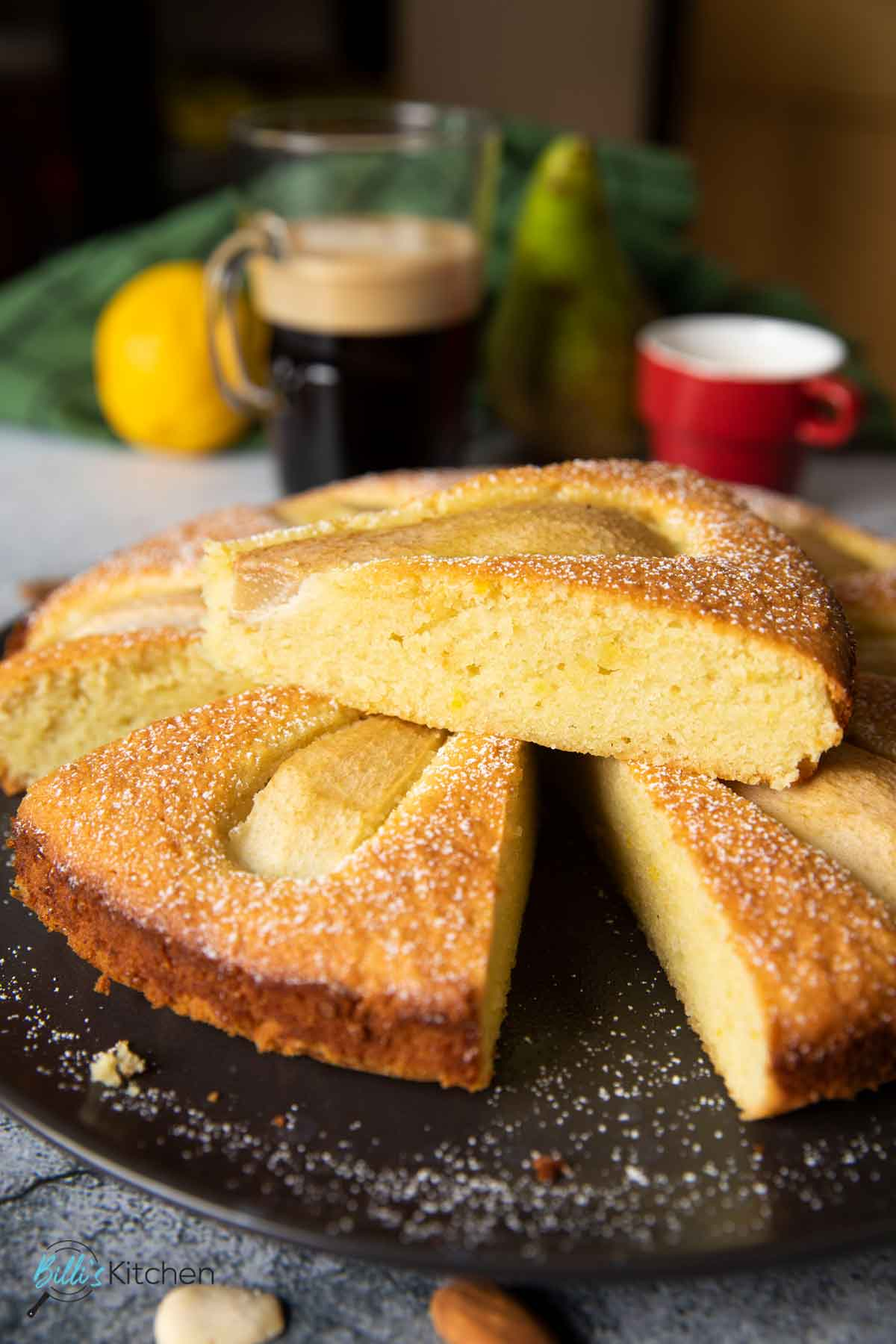 A closer image of a slice of Rustic Almond Pear Cake, highlighting the texture of the cake, with a tall glass of coffee and an espresso on the side.