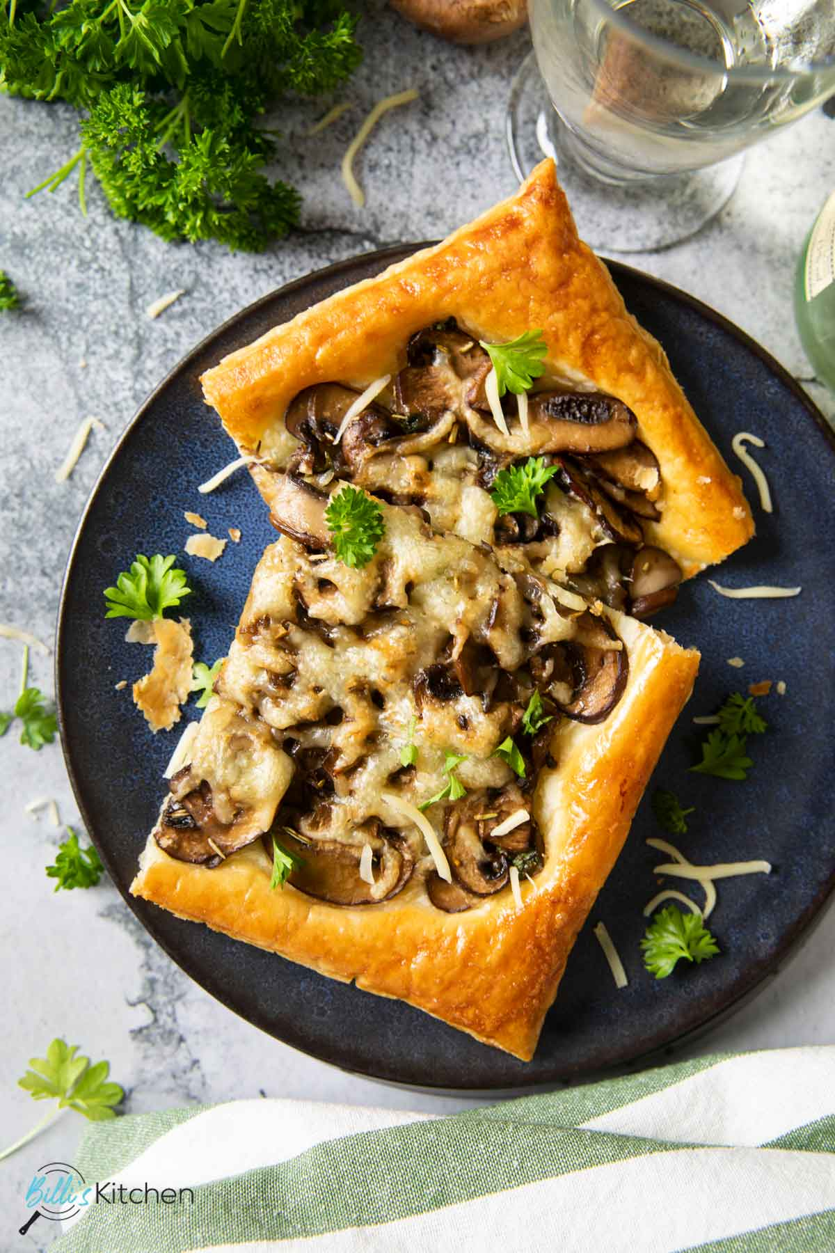 A couple of slices of mushroom tart, served with a glass of white wine.