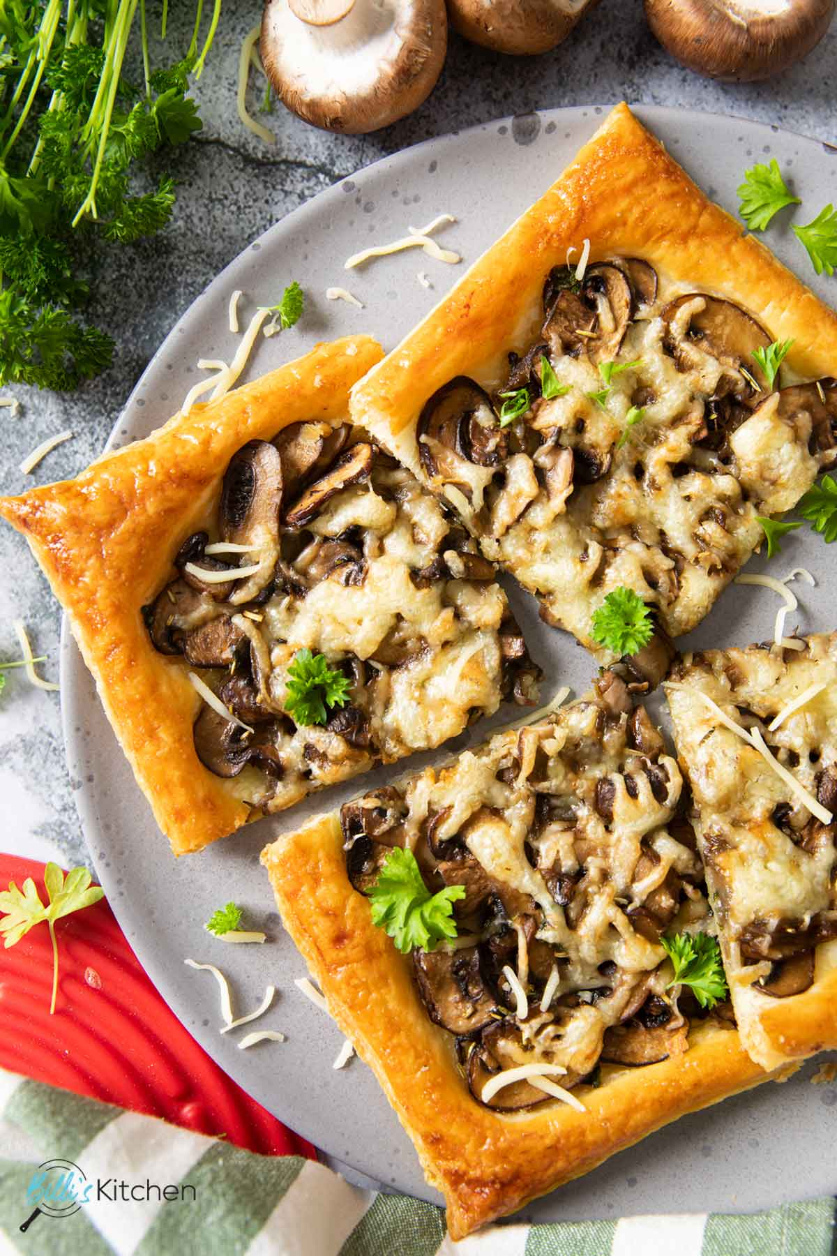An overhead shot of slices of mushroom tart on a plate, with some shredded cheese and fresh parsley on top; cremini mushrooms are next to the plate.