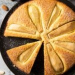 An overhead shot of fresh pear cake, with a slice ready for serving, sprinkled with powdered sugar.