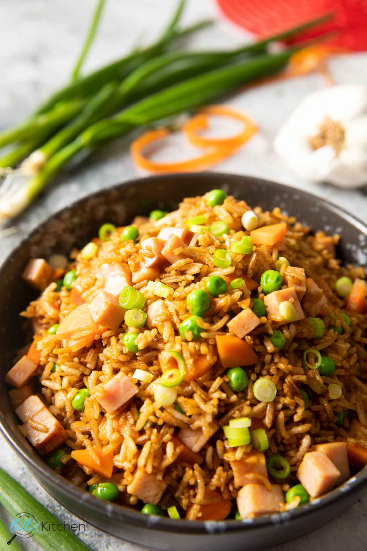 A shot of fried rice with ham, ready for serving, with spring onions on the background.