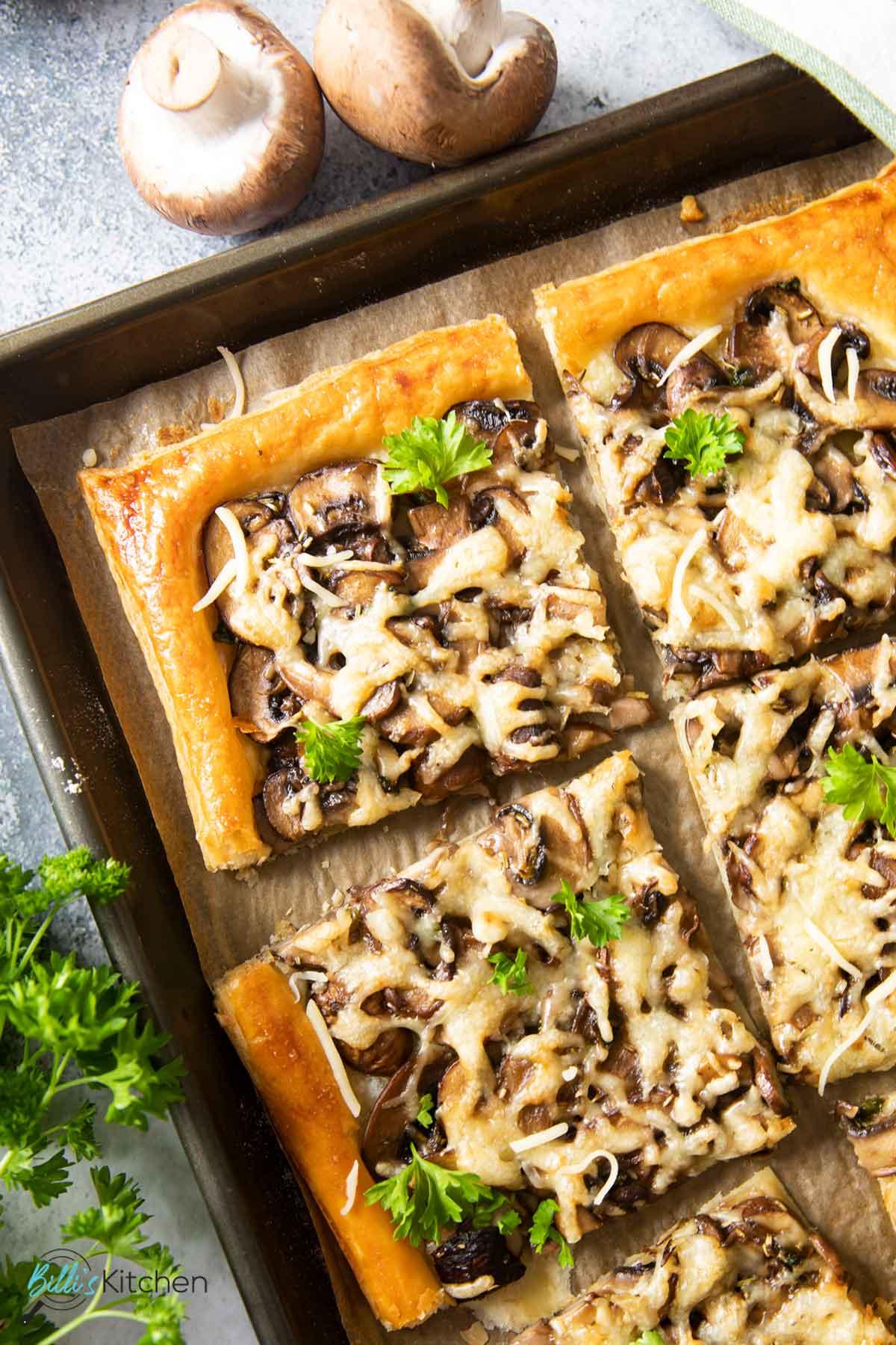 An overhead shot of slices of mushroom tart, with fresh mushrooms on the side.