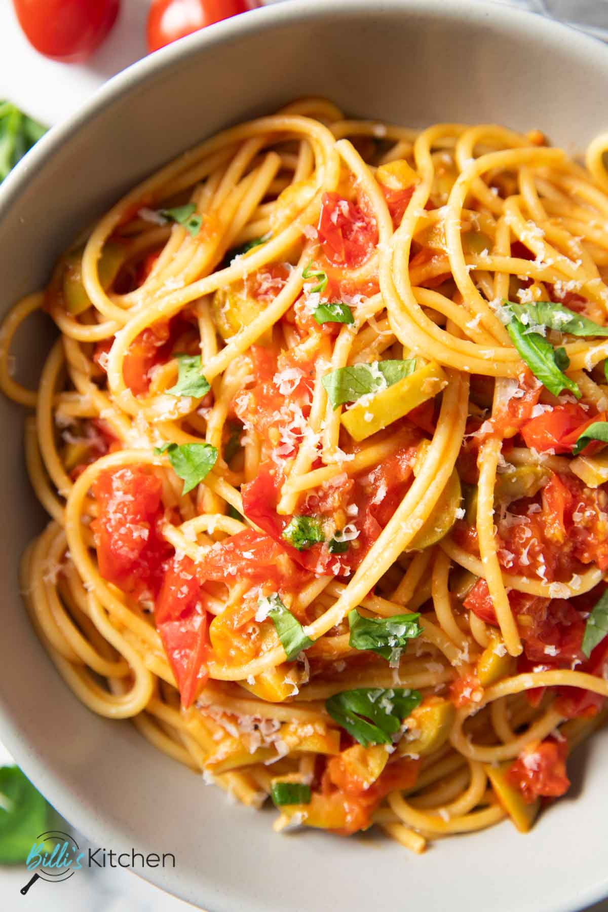 A closer shot of a plate of cherry tomato pasta, highlighting the texture of the dish.