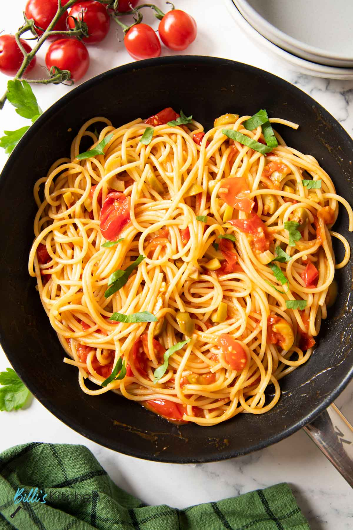 A pan of pasta with cherry tomatoes, with fresh tomatoes on the side.