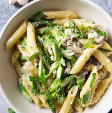 An overhead shot of a serving of pasta with mushrooms and asparagus, with fresh button mushrooms in the background.