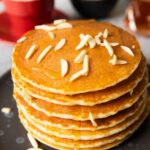 A stack of gluten-free rice flour pancakes, with almond slices on top wiht honey-