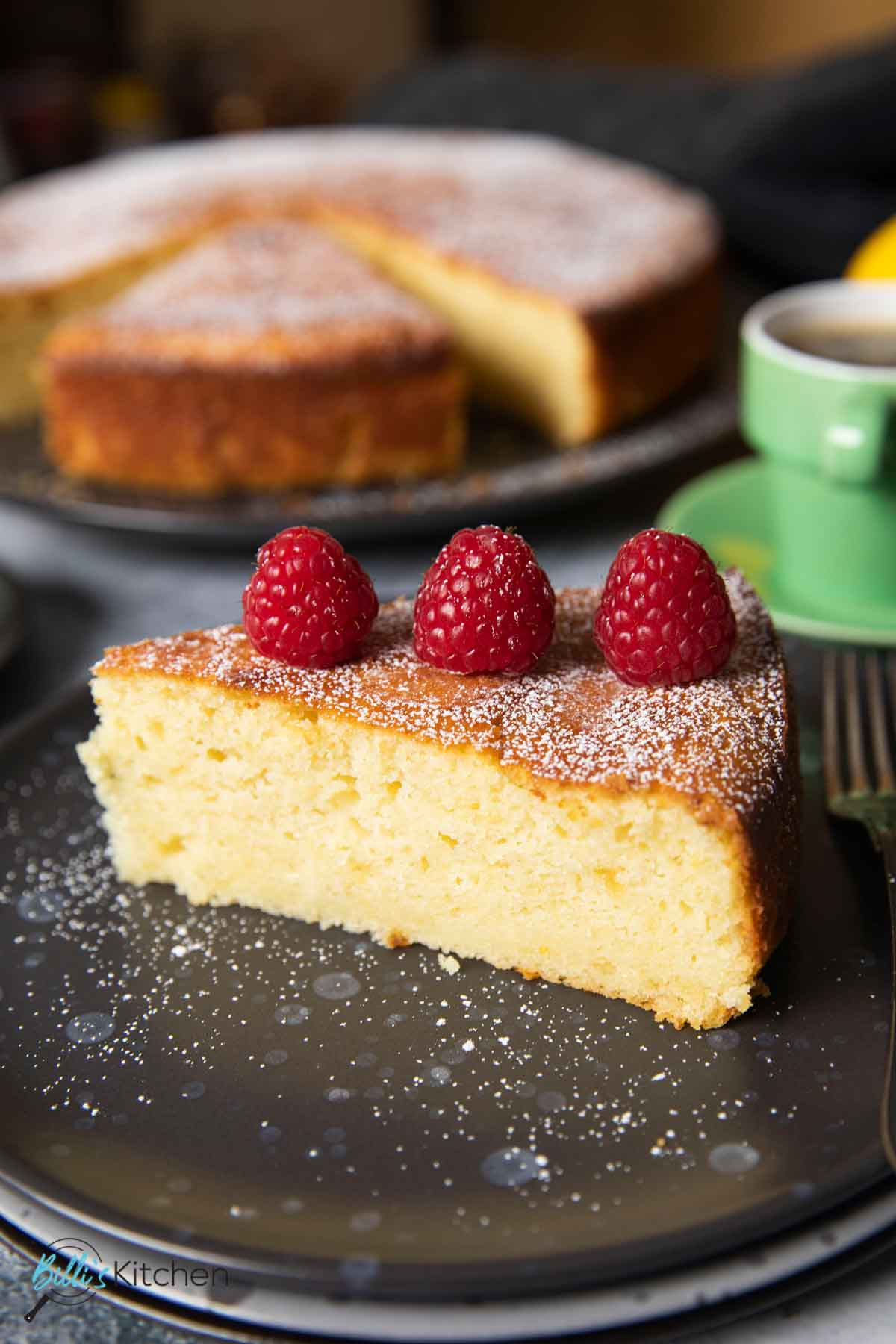 An image showing a slice of lemon ricotta cake served with fresh raspberries on top, and a cup of espresso.