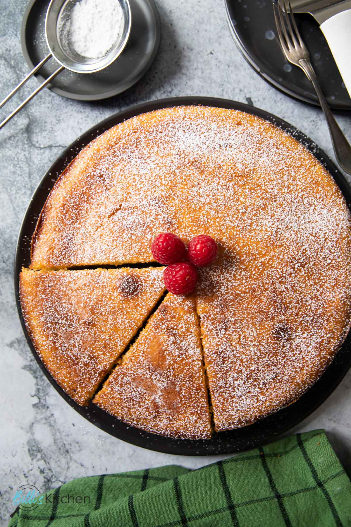 An overhead shot of freshly baked lemon ricotta cake, dusted with powdered sugar and with couple of slices ready for serving.