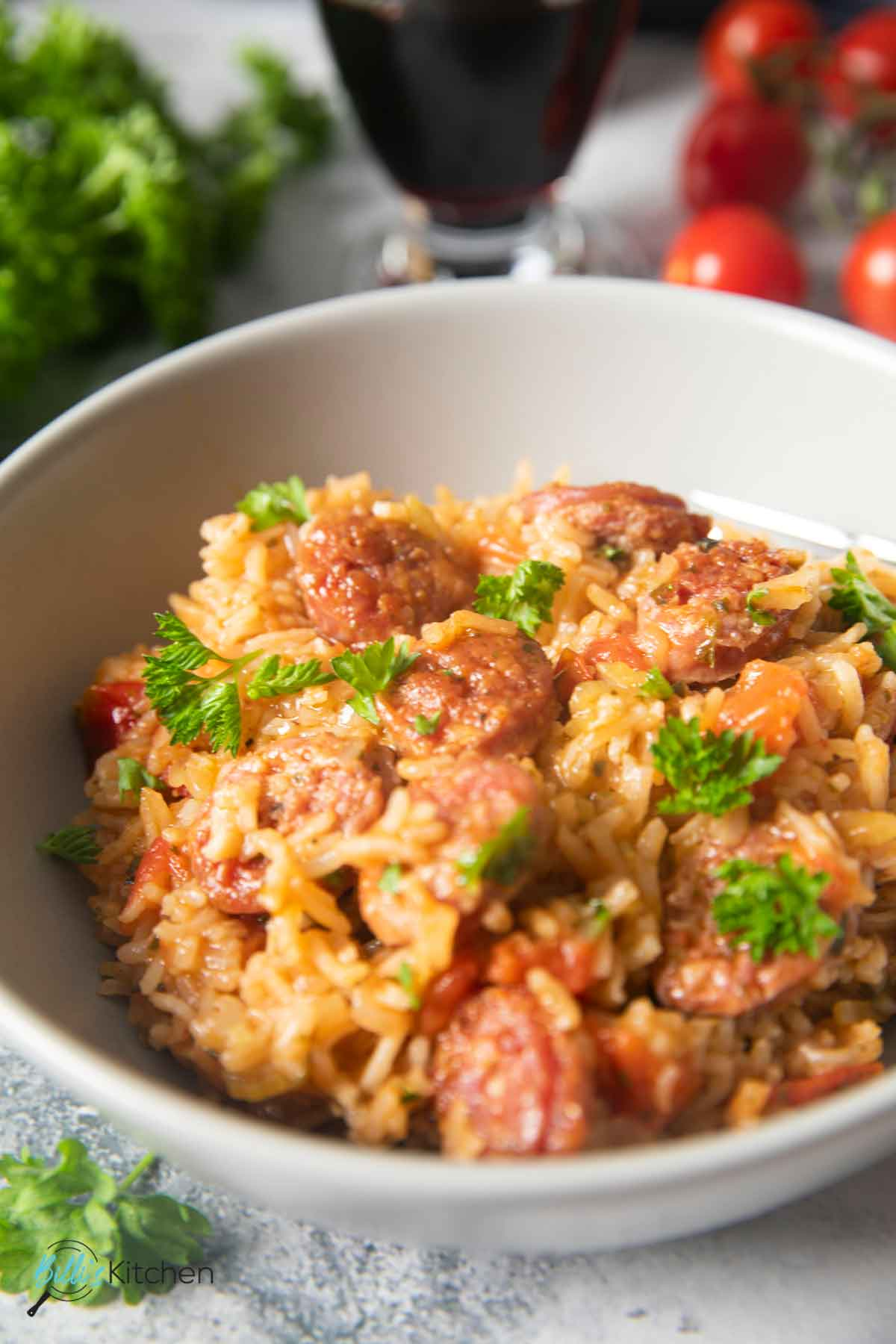 A closer shot of a plate of sausage and rice, with fresh cherry tomatoes and parsely on the background.