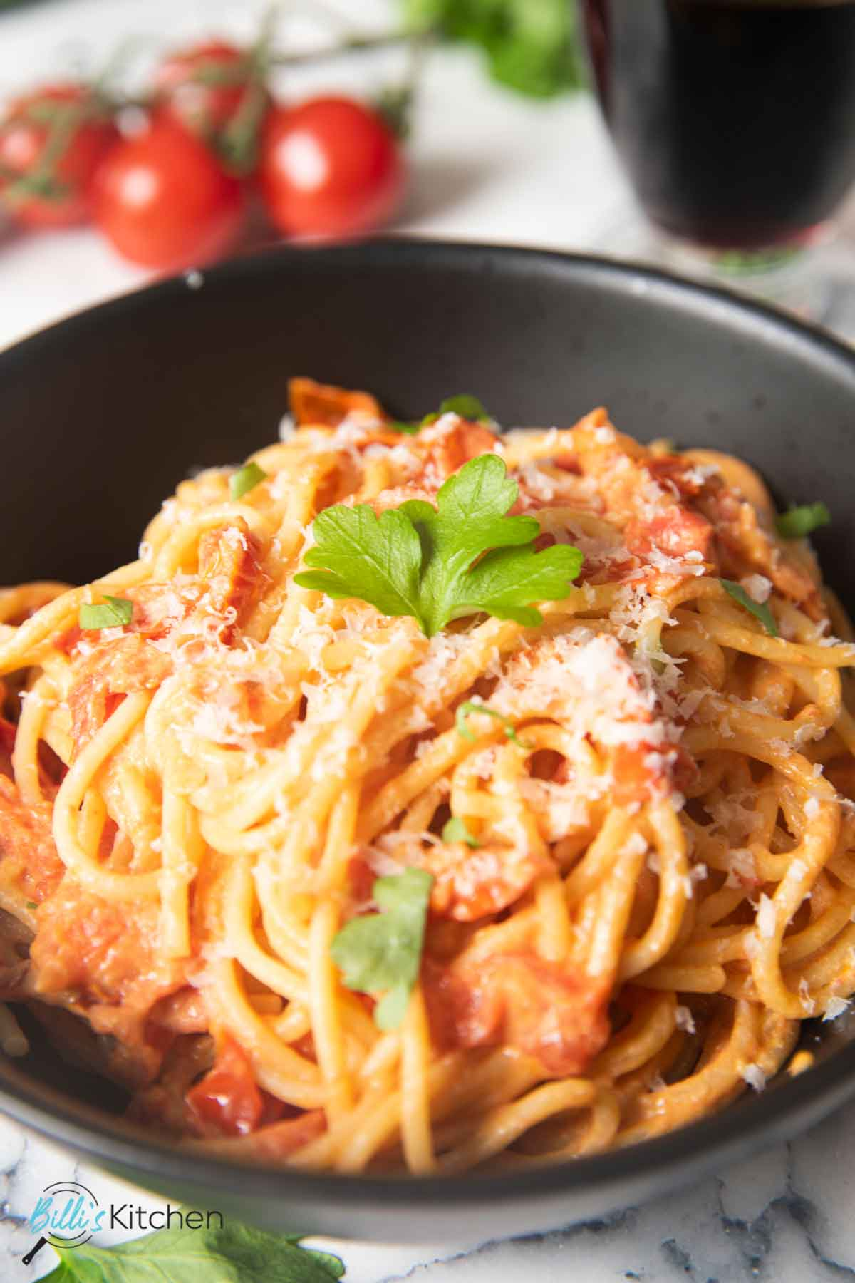 A closer shot of a bowl of tomato and mascarpone pasta, with grated Parmigiano Reggiano on top.