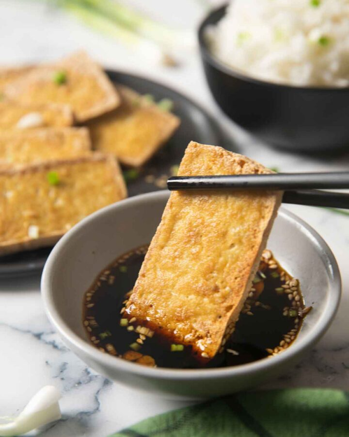 An image showing cripy tofu being dipped in the soy sauce, with white rice on the background.
