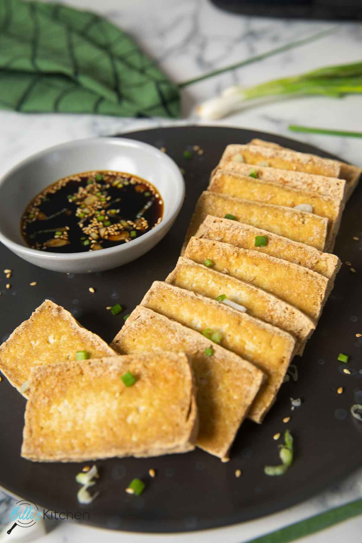 Crispy, fried tofu served with soy dipping sauce, garnished with spring onions.