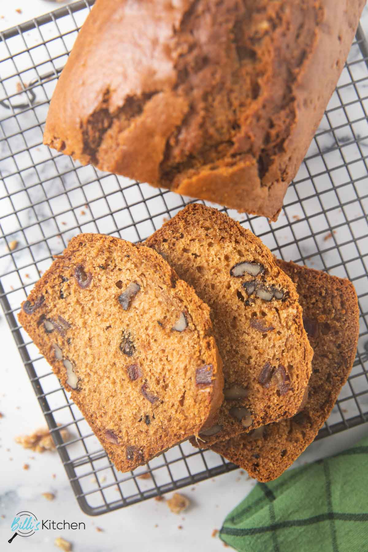 An overhead shot of slices of date and nut bread on a cooling rack.