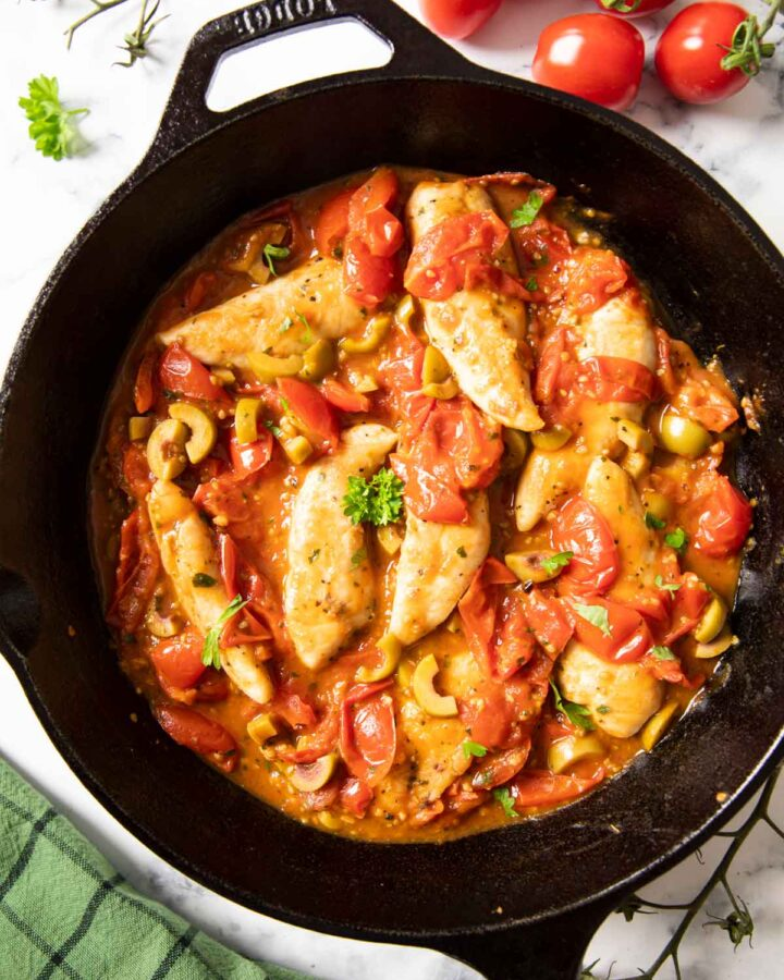 An overhead shot of a pan of chicken and cherry tomatoes, with some fresh cherry tomatoes on the side.