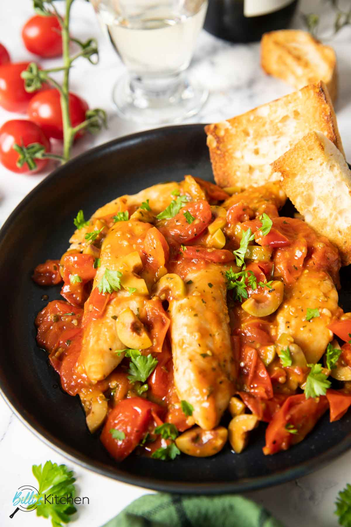 A close shot of a serving of chicken and tomatoes, showing the burst tomatoes and the chopped olives in the sauce.