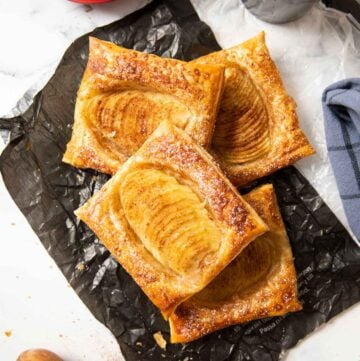 An overhead shot of freshly baked pear puff pastry tarts served with coffee.
