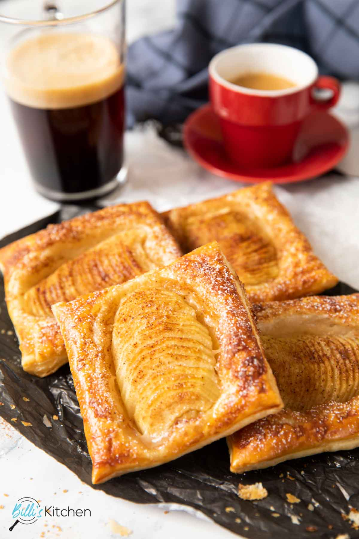 Pear tarts with puff pastry, lightly dusted with powdered sugar, served with espresso and coffee.
