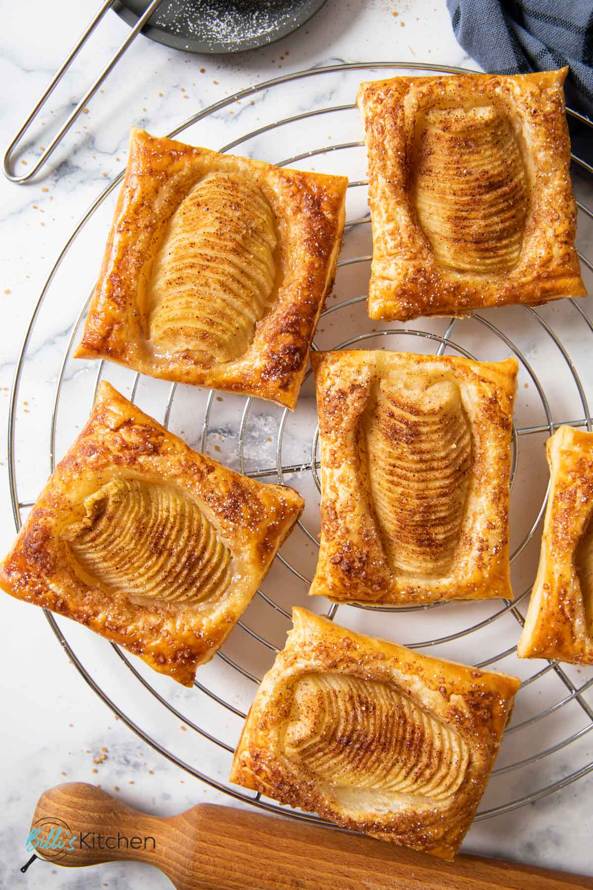 Freshly baked pear tarts on a cooling rack.