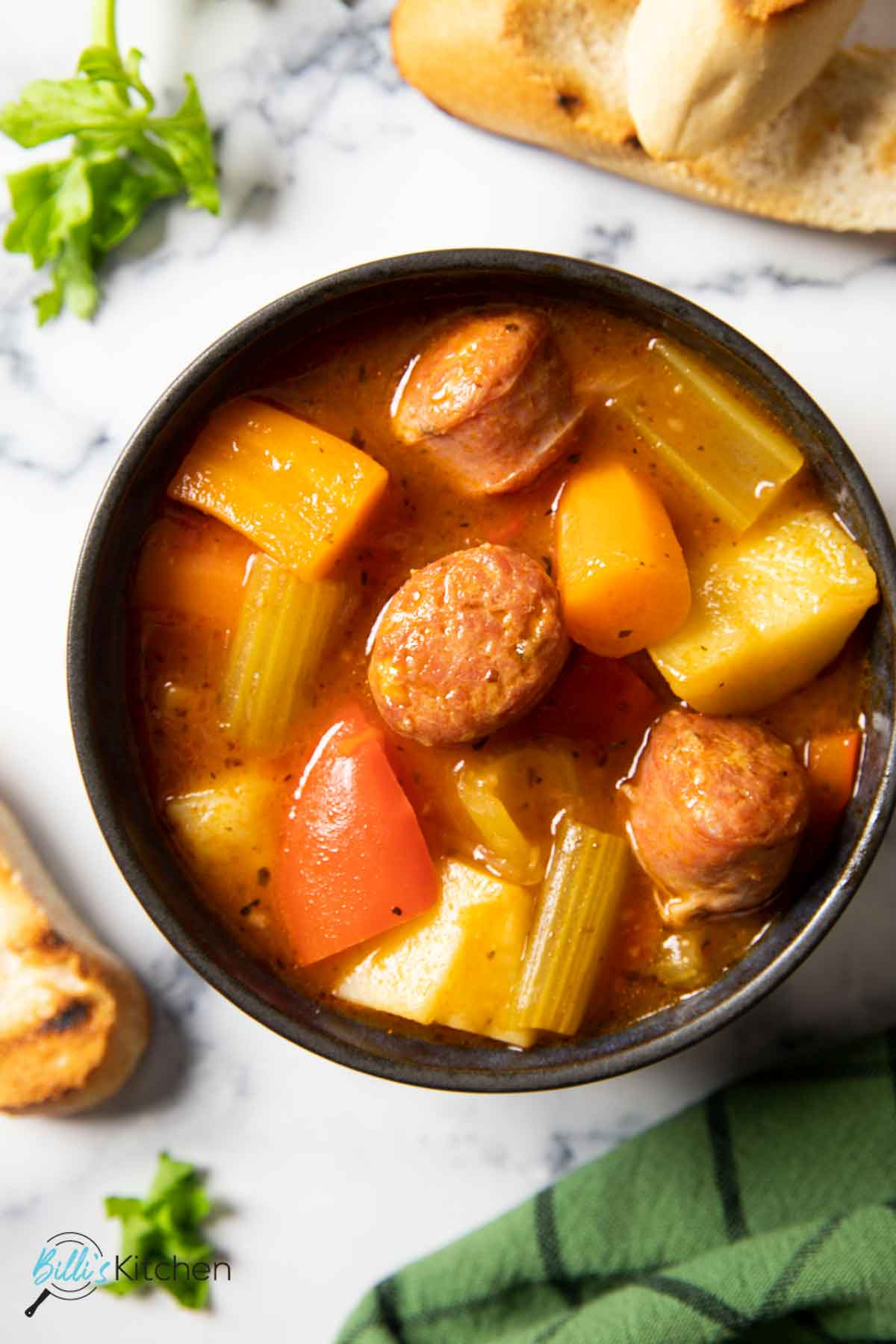 An overhead shot of a bowl of Italian sausage stew with vegetables with some chunky bread on the side.