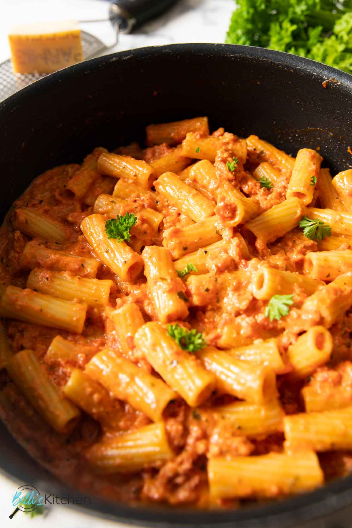 A close shot of a pan of spicy Italian sausage pasta, ready for serving.